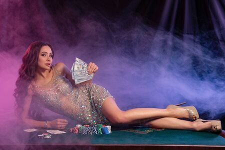 Girl in golden dress playing poker at casino, holding money, laying on table with chips, cards on it. Black, smoke background. Gambling. Close-up.