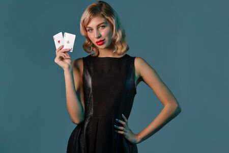 Blonde girl in black stylish dress showing two playing cards, posing against blue background. Gambling entertainment, poker, casino. Close-up.