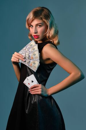 Blonde girl in black stylish dress holding some money and cards, posing against blue background. Gambling entertainment, poker, casino. Close-up.