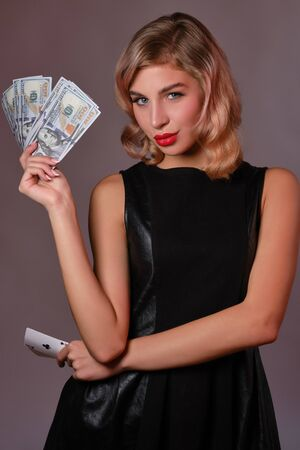 Blonde girl in black stylish dress holding some money and cards, posing against gray background. Gambling entertainment, poker, casino. Close-up. Stok Fotoğraf
