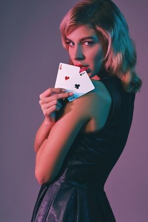 Blonde girl in black stylish dress showing two playing cards, posing against colorful background. Gambling entertainment, poker, casino. Close-up. Stok Fotoğraf