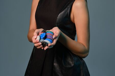 Girl in black leather dress holding some colorful chips, posing against gray background. Gambling entertainment, poker, casino. Close-up.