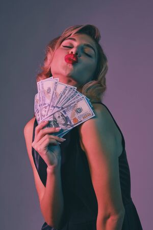 Blonde girl in black stylish dress holding some money, posing against colorful background. Gambling entertainment, poker, casino. Close-up.