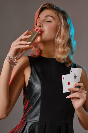 Blonde girl in black dress holding two playing cards and drinking champagne, posing against gray background. Gambling, poker, casino. Close-up.
