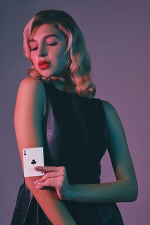 Blonde girl in black stylish dress showing ace of clubs, posing against colorful background. Gambling entertainment, poker, casino. Close-up.