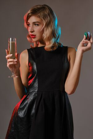 Blonde girl in black dress holding glass of champagne and chips, posing against gray background. Gambling, poker, casino. Close-up.