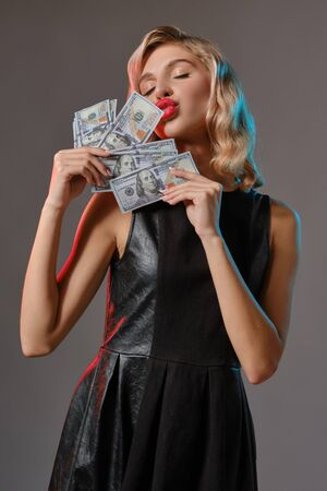 Blonde girl in black stylish dress holding and kissing some money, posing against gray background. Gambling entertainment, poker, casino. Close-up. Stok Fotoğraf