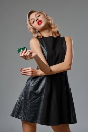Blonde girl in black leather dress holding some colorful chips, posing against gray background. Gambling entertainment, poker, casino. Close-up. Stok Fotoğraf