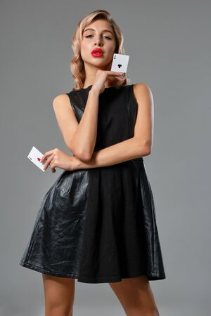 Blonde girl in black stylish dress showing two playing cards, posing against gray background. Gambling entertainment, poker, casino. Close-up.
