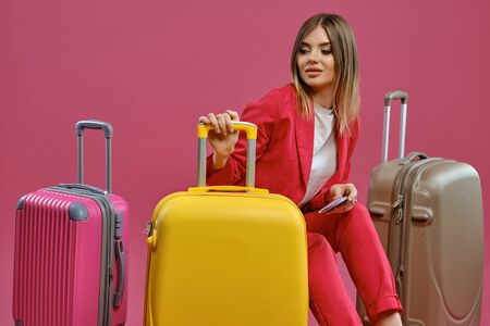 Blonde female sitting among colorful suitcases