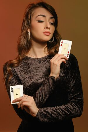 Brunette female in black velvet dress and jewelry showing two cards Stok Fotoğraf