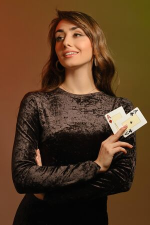 Brunette female in black velvet dress and jewelry showing two cards
