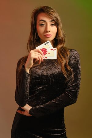 Brunette female in black velvet dress and jewelry showing two cards 版權商用圖片