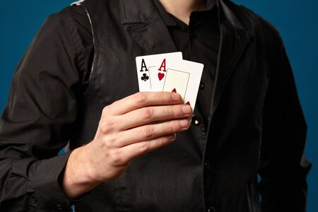 Holding two playing cards, aces, while posing against blue studio Imagens