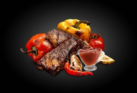 Grilled pork or beef steaks with bell pepper, zucchini, tomato, chilli, half of garlic and red sauce in glass gravy boat, black background. Close up Stockfoto