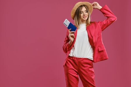 Blonde female in straw hat, white blouse and red pantsuit. Smiling, holding passport and ticket while posing against pink studio background. Close-up Reklamní fotografie