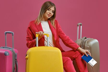 Blonde woman in red pantsuit, white blouse. She is smiling while sitting among colorful suitcases, holding passport and ticket, pink background
