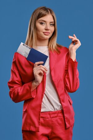 Blonde female in white blouse and red pantsuit. She smiling, holding passport and ticket while posing on blue studio background. Close-up
