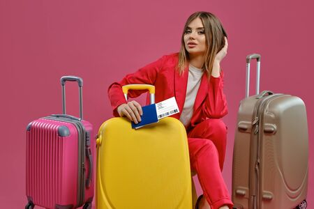 Blonde lady in red pantsuit, white blouse. She touching hair, sitting among colorful suitcases, holding passport and ticket, pink background