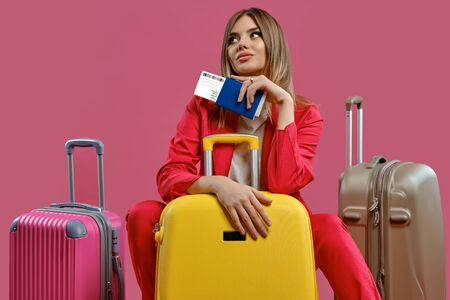 Blonde girl in red pantsuit, white blouse. She looking thoughtful, sitting among colorful suitcases, holding passport and ticket, pink background
