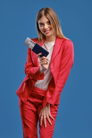 Blonde girl in white blouse and red pantsuit. She smiling, holding passport and ticket while posing on blue studio background. Close-up Reklamní fotografie