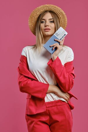 Blonde model in straw hat, white blouse and red pantsuit. She is holding passport and ticket while posing against pink studio background. Close-up Reklamní fotografie