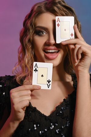 Brown-haired female in black shiny dress is smiling, showing two playing cards, posing on colorful background. Gambling, poker, casino. Close-up.