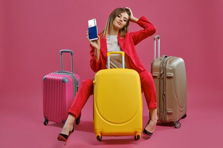 Blonde woman in red pantsuit, white blouse, black heels. She smiling, sitting among colorful suitcases, holding passport and ticket, pink background