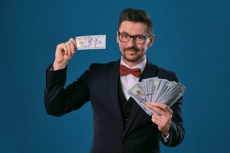 Man in black classic suit, red bow-tie, glases is holding some dollar bills, posing on gray studio background. Gambling, poker, casino. Close-up.