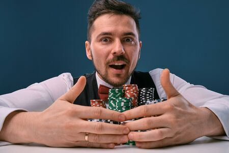 Man in black vest and shirt sitting at white table with stacks of chips on it, posing on blue studio background. Gambling, poker, casino. Close-up.
