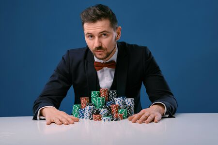 Man in black suit is sitting at white table with colored stacks of chips on it, posing on blue studio background. Gambling, poker, casino. Close-up.