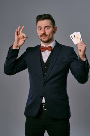 Man in black classic suit and red bow-tie showing two playing cards and chips, posing on gray studio background. Gambling, poker, casino. Close-up. Standard-Bild