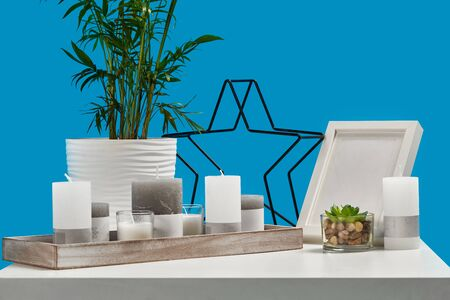 White table with green plants in pots, some candles in a wooden stand, decorative black iron star and empty photo frame. Blue background. Close up