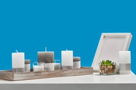 White table with green succulent in glass pot, some different sized candles in a wooden stand and empty photo frame. Blue background. Close up Фото со стока - 140948825