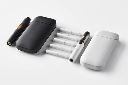 New generation, black and white, two electronic cigarettes and two batteries, five heatsticks isolated on white. New alternative technology. Hi-tech heating tobacco system. Workspace mock up. Close up