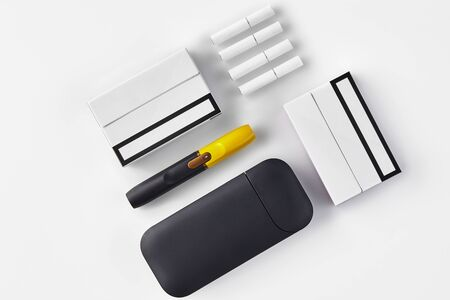 Black and yellow electronic cigarette, battery, two packs and four heatsticks isolated on white. Hi-tech heating tobacco system. Tools used to help stop smoking. Close up, copy space, flat lay