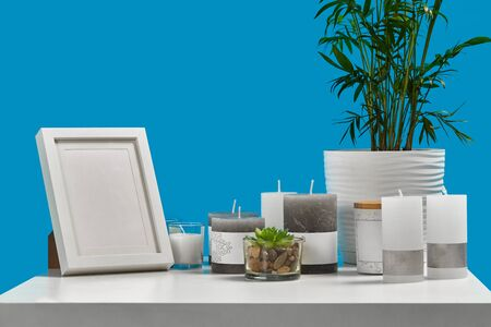 White table with green plant and succulent in pots, some different sized and colors candles, empty photo frame, jar with a wooden lid and copy space. Blue background. Interior design. Close up Фото со стока - 140949075