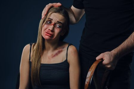 Cruel man put his hand on female head, showing belt. Victim with bruises on face sitting nearby. Blue background. Domestic violence. Close-up.