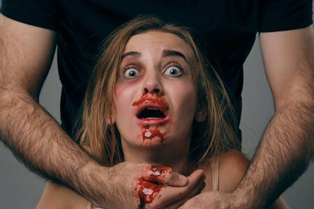 Strong man strangling scared female with bruises on her face. Blood from her mouth flows down his arm. Gray background. Domestic violence. Close-up.