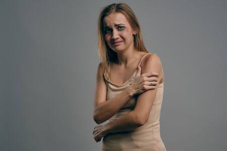 Blonde girl with bruises on her face posing against gray studio background. Domestic violence, abuse. Depression, despair. Close-up, copy space.