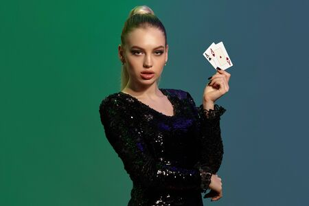 Blonde woman in jewelry and black sequin dress. Showing two aces, propping her elbow with hand, posing on colorful background. Poker, casino. Close-up Stok Fotoğraf
