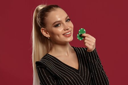Blonde woman with ponytail, in black dress in rhinestones. She is smiling, showing two green chips, posing on red background. Poker, casino. Close-up