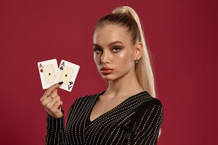 Blonde woman in black dress in rhinestones. Showing two playing cards, posing against red background. Gambling entertainment, poker, casino. Close-up 写真素材 - 142143405