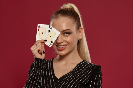 Blonde lady in black dress in rhinestones. She is smiling, showing two aces, posing against red background. Gambling, poker, casino. Close-up