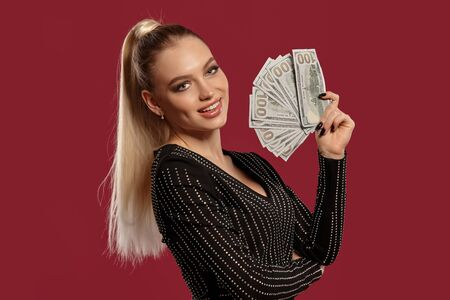 Blonde lady in black dress in rhinestones. Showing fan of hundred dollar bills, smiling, posing sideways on red background. Poker, casino. Close-up Stok Fotoğraf