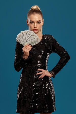 Blonde woman with ponytail, in black sequin dress. Showing fan of hundred dollar bills, posing on blue background. Gambling, poker, casino. Close-up