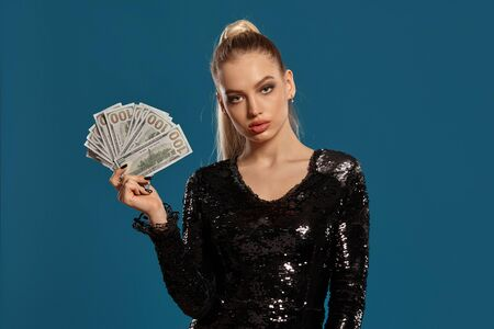 Blonde lady with ponytail, in black sequin dress. Showing fan of hundred dollar bills, posing on blue background. Gambling, poker, casino. Close-up Stok Fotoğraf