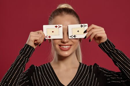 Alluring blonde girl with ponytail, in jewelry and black dress in rhinestones. She has closed her eyes with two playing cards, smiling, posing against red background. Gambling, poker, casino. Close-up