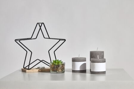 Table with green succulent in glass pot, three different sized candles, one small in candlestick in form of iron star on wooden stand. Isolated on white. Interior design. Close up, copy space