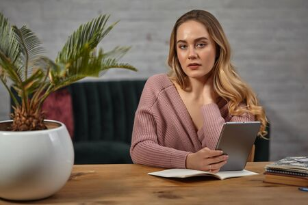 Lady blogger in pink cardigan is holding a tablet. Sitting at wooden table with notebooks and palm tree in pot on it. Student, blogger. Close-up